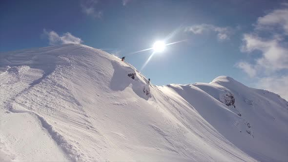 Thumbnail for A photographer photographing skiers skiing on snow covered mountains.