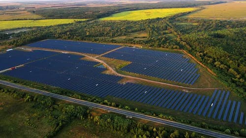 Solar Panels in the Lines on the Field Near the Highway