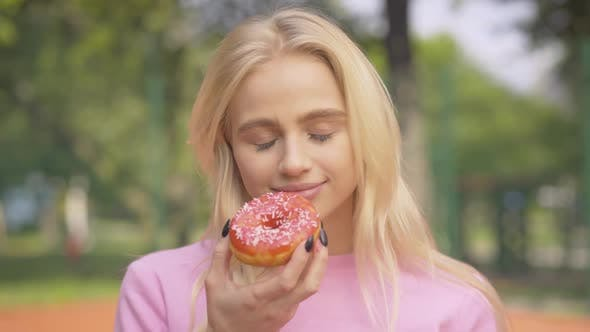 Thumbnail for Portrait of Cheerful Blond Woman Biting Sweet Donut and Laughing. Happy Beautiful Caucasian Lady