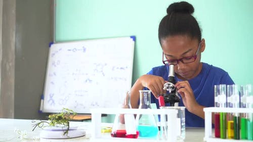 Young African American Kid Using Microscope in Lab