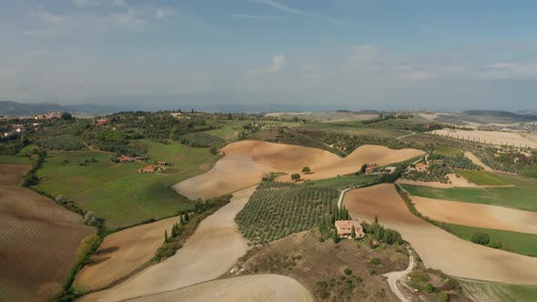 Aerial View of a Rural Landscape in Tuscany. Rural Farm, Vineyards, Cypress Trees, Sunlight and