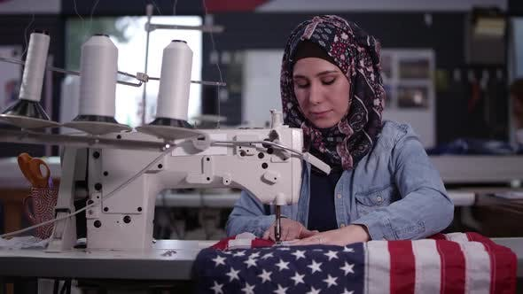 Thumbnail for Woman wearing headscarf sewing American Flag