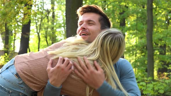Thumbnail for A Man Sits in a Park on a Sunny Day, a Woman Surprises Him with a Hug From Behind and They Talk