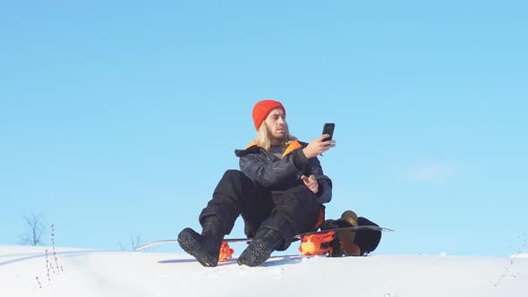 Thumbnail for Positive Sporty Man Is Taking Photoes on the Top of Snowy Mountain