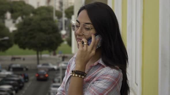 Thumbnail for Smiling Brunette in Eyeglasses Standing on Balcony and Talking on Phone.
