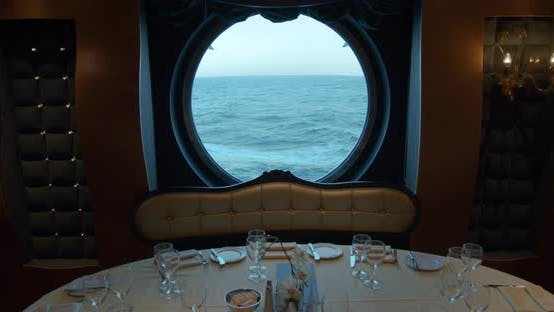 Thumbnail for A Served Table in a Restaurant Against the Backdrop of a Huge Round Window on a Cruise Ship