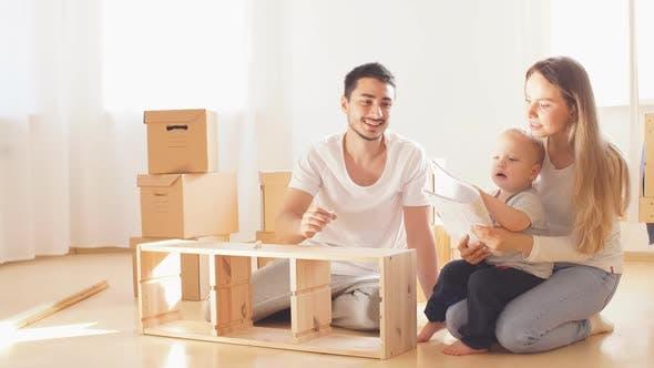 Familie Leseanleitung und Montage von Möbeln zusammen im Wohnzimmer der neuen Wohnung Pile