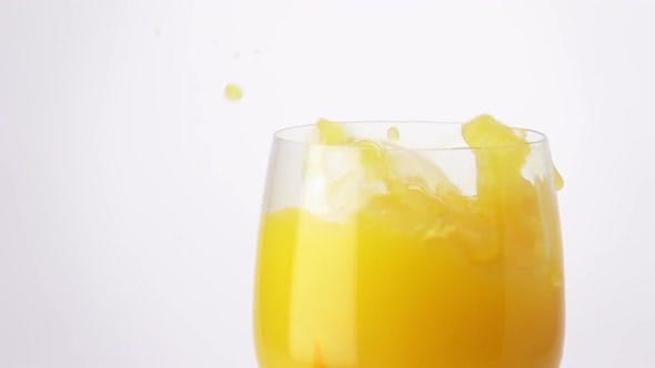 Thumbnail for Slice of Orange Falling into a Glass of Orange Juice