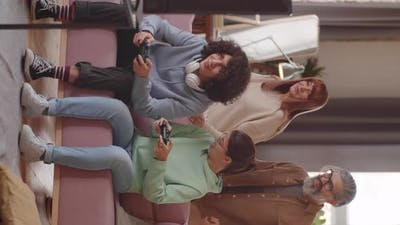 Happy Teenage Children Playing Video Game with Support of Parents