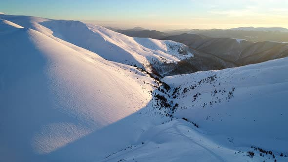 Thumbnail for Flight Over the Snowy Mountains Illuminated By the Evening Sun