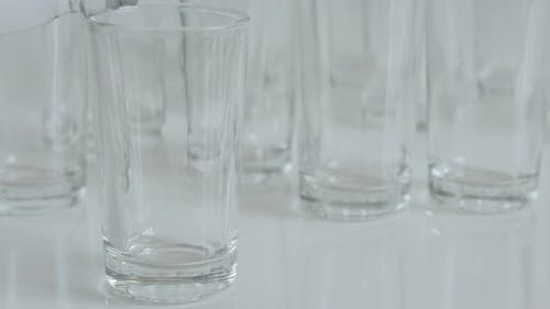 Close-up pouring shot glasses on white background with vodka 4K 2160p 30fps UltraHD footage - Fillin