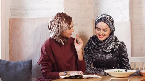 Thumbnail for Two Young Beautiful Muslim Business Women in Hijab Working with Documents in Cafe.