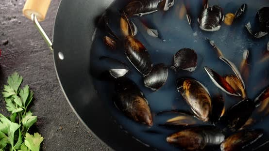 Fragrant Mussels in a Saucepan. On a Black Background.