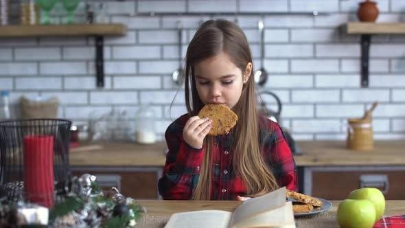 Thumbnail for Kleine schöne Mädchen sitzen auf dem Küchentisch, Essen Kekse und Blättern durch Buch
