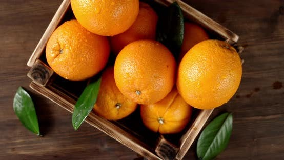 Juicy Oranges with Leaves in a Wooden Box Slowly Rotate