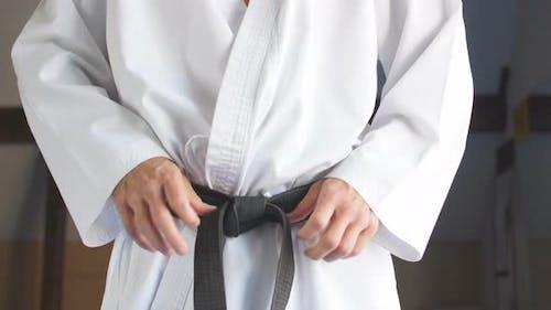 Hände Anziehen schwarzen Gürtel auf Mann gekleidet in Kimono