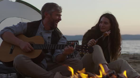 Thumbnail for Romantic Man Playing Guitar for Girlfriend by Campfire at Picnic on Beach