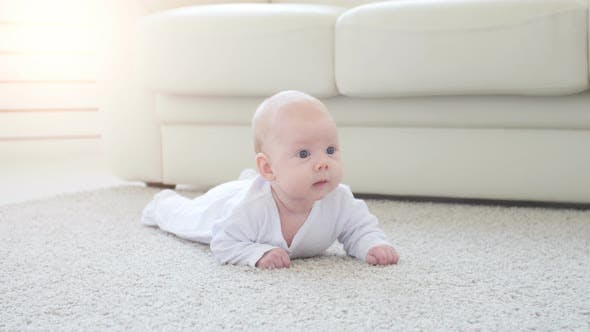Thumbnail for Happy Baby Lying on Carpet Background, Smiling Infant Kid Girl in White Clothing