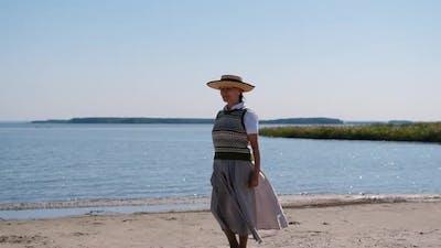 An Elderly Woman Walks By the Sea or Ocean