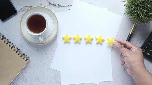 Customer Review Concept with Rating Golden Stars on Table