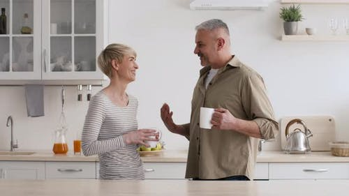 MiddleAged Couple Having Coffee Talking Standing In Kitchen At Home