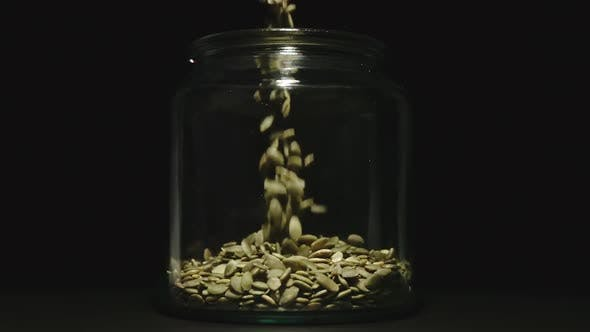 Thumbnail for Peeled Pumpkin Seeds Fall Into Empty Glass Jar On Black Background - Front View
