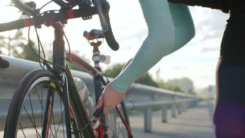 Female Racer Inflating Bicycle Tires