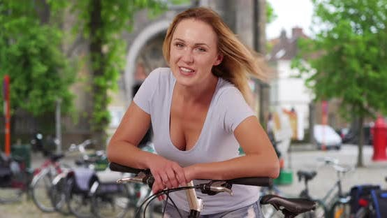 Thumbnail for Caucasian lady posing with bicycle outside with wind blowing through her hair