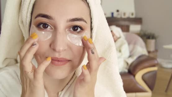 Cover Image for Closeup Face of a Cute Caucasian Woman with Brown Eyes in Hair Towel Applying Eye Gel Patches
