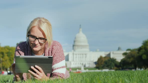 Thumbnail for A Woman Lies on a Lawn Against the Background of the Capitol in Washington, DC. Uses a Tablet