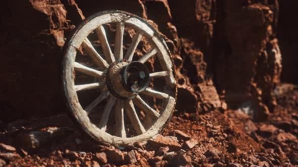Old Wooden Cart Wheel on Stone Rocks