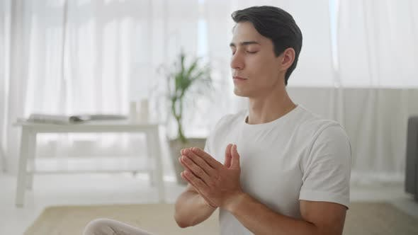Thumbnail for Close Up Relaxed Young Man in Sportswear Is Meditating in Lotus Position Sitting on Yoga Mat With