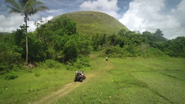 Thumbnail for Aerial view two quadricycles doing trail next Chocolate Hills Complex, Batuan.