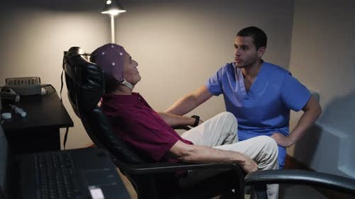 Senior man with a doctor in geriatric hospital for medical test using EEG.