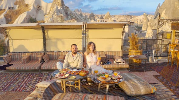 Happy couple on rooftop of an cave house enjoying brackfast and of Goreme city panorama Cappadocia