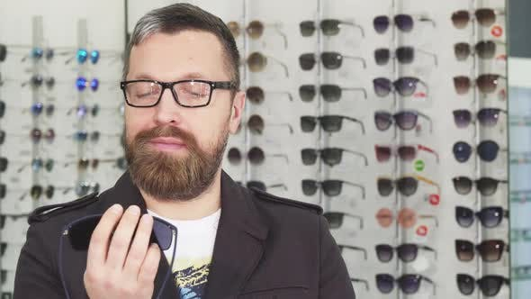 Thumbnail for Mature Man Choosing Between Two Pairs of Sunglasses at the Store