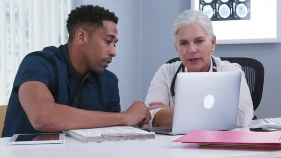 Thumbnail for Portrait of doctor and patient using notebook computer inside doctors office