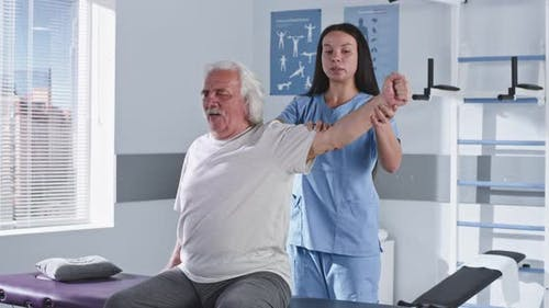 Rehabilitation Therapist Stretching Arm of Elderly Man