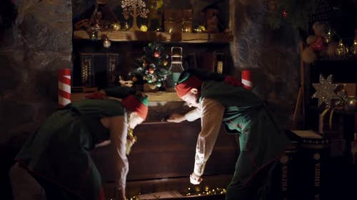 Curious elves in small decorated room opening the magic box. Two elves in fairy suits