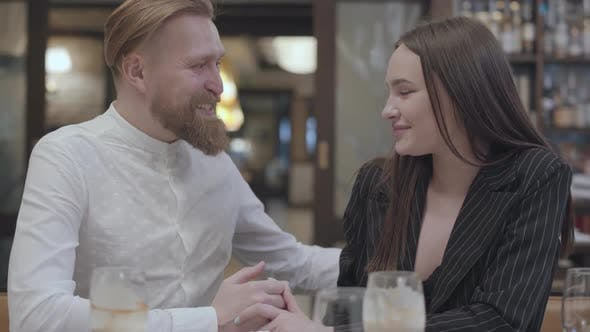 Thumbnail for Glamour Brunette Woman and a Handsome Bearded Blond Man Sitting at the Table