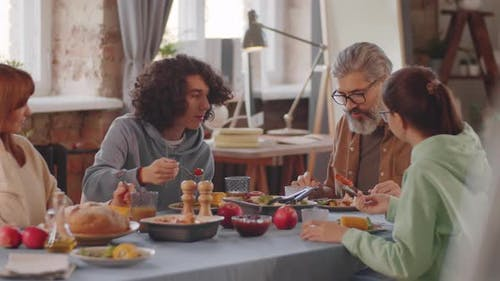 Family Having Conversation over Dinner at Home