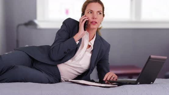Thumbnail for Successful woman lying on bed, making phone call while working on laptop