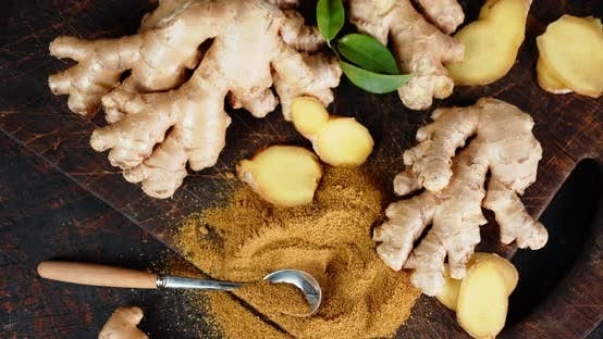 Powder Ground Ginger with a Spoon on Wooden Cutting Board Rotates Slowly