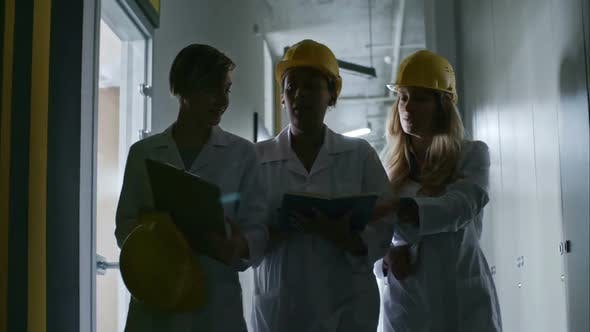 Thumbnail for Female Chief Engineer Walking with Colleagues through Corridor
