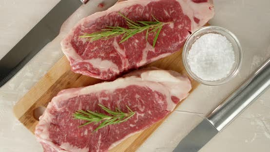 Raw Steak Beef Striploin with Rosemary Slowly Rotates.