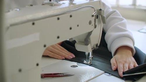 Eine weibliche Hand schiebt Material durch eine Nähmaschine