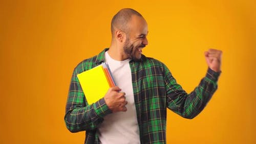 Male African American Student Holding Books and Celebrating Success Against Yellow Background