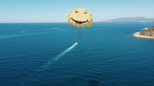 Drone flight next to parachutists engaged in parasailing. The parachute is tied to a motor boat.