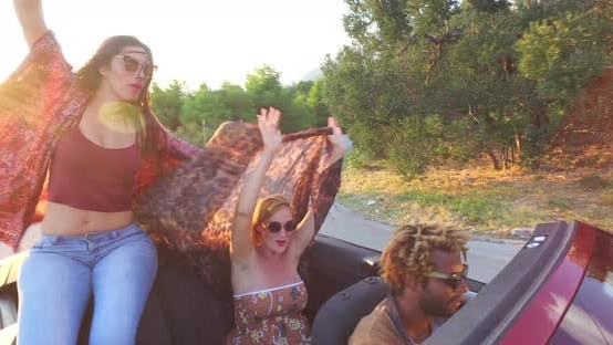 Thumbnail for Attractive caucasian women waving their scarves while riding in convertible