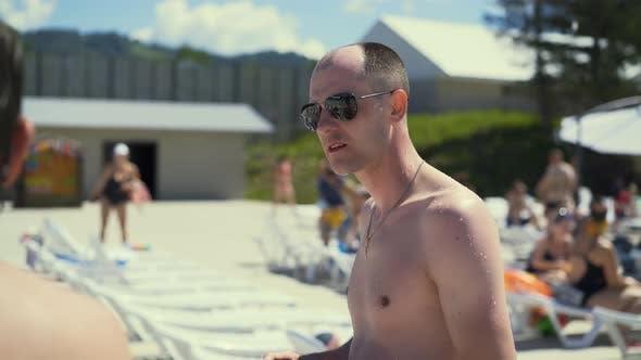 Closeup Travelling Dialog Bald Italian Man Stands on Beach Wearing Sunglasses Looks Like Mob